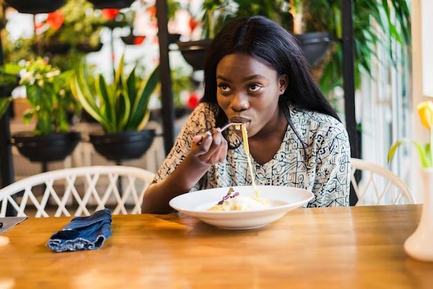 Mulher bonita africana comendo macarrão e bebendo vinho no restaurante italiano