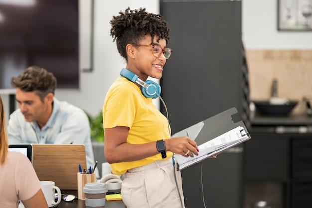 Mulher bonita afro-americana com fones de ouvido e óculos, vista em coworking mulher bonita afro-americana com fones de ouvido e óculos, vista em coworking