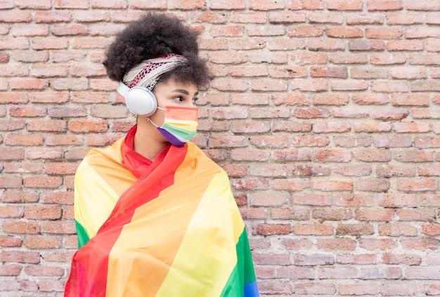 Mulher bonita afro com fones de ouvido e máscara lgbt
