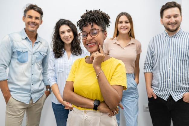 Mulher bonita afro em coworking com colegas, líder, chefe