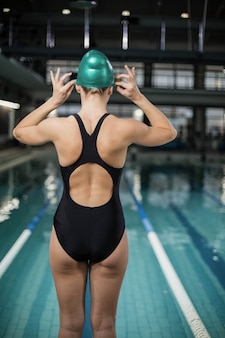 Mulher bonita, ajustando sua touca de banho na piscina