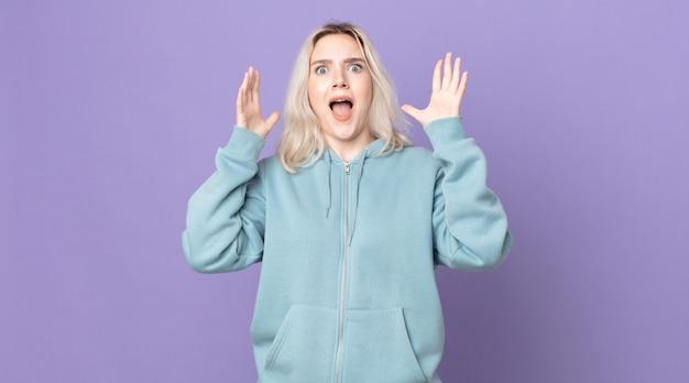 Mulher bonita albina gritando com as mãos para o alto, sentindo-se furiosa, frustrada, estressada e chateada
