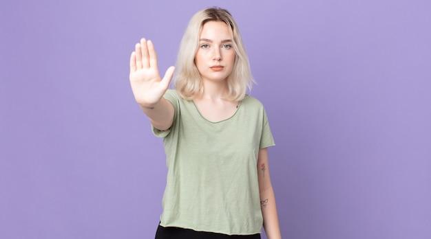 Mulher bonita albina parecendo séria, severa, descontente e irritada mostrando a palma da mão aberta fazendo gesto de pare