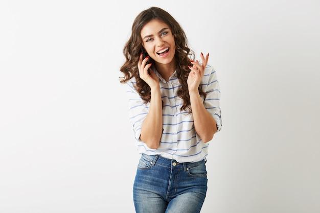 Mulher bonita alegre com expressão facial animada rindo e falando ao telefone, sorrindo sinceramente, cabelo longo cacheado, estilo estudante, isolado, dentes brancos, senhora emocional