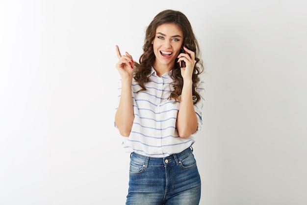 Mulher bonita alegre com expressão facial exaltada mostrando dedo, gesticulando, rindo e falando ao telefone, sorrindo sinceramente, cabelo longo cacheado, estilo estudante, isolado, dentes brancos, senhora emocional