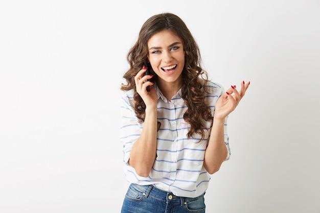 Mulher bonita alegre com expressão facial exultante rindo e falando ao telefone, sorrindo sinceramente, cabelo longo cacheado, estilo estudante, isolado, dentes brancos, senhora emocional
