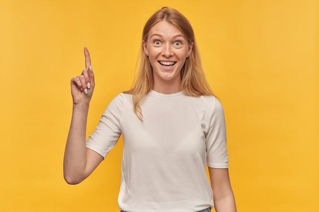 Mulher bonita alegre com sardas em camiseta branca apontando para o céu e tendo uma ideia em amarelo