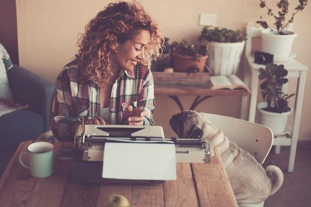 Mulher bonita alegre com seu adorável cachorro pug em casa enquanto escreve para o trabalho com a velha máquina de escrever e aproveita a atividade de lazer interna com uma xícara de chá - conceito de trabalho e melhor amigo animal