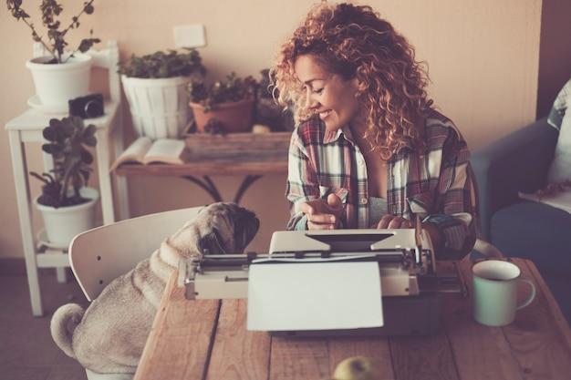 Mulher bonita alegre com seu adorável cão pug em casa enquanto escreve para o trabalho com a velha máquina de escrever e desfruta da atividade de lazer interna com uma xícara de chá