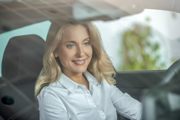Mulher bonita alegre dirigindo um carro