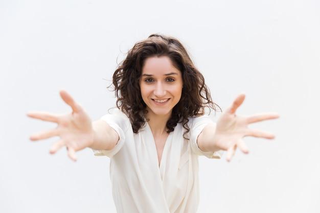 Mulher bonita alegre feliz que outstretching as mãos