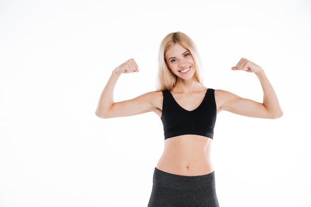 Mulher bonita alegre fitness mostrando seu bíceps