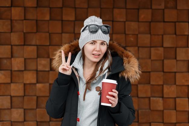 Mulher bonita alegre jovem hippie no chapéu de malha vintage com uma elegante jaqueta de inverno com peles em um moletom cinza da moda fica perto da parede. garota feliz sorri e mostra um sinal de paz.