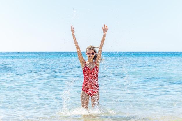 Mulher bonita alegre que espirra no mar, jogando e rindo