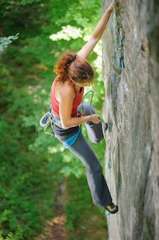 Mulher bonita alpinista escalando rocha íngreme com corda