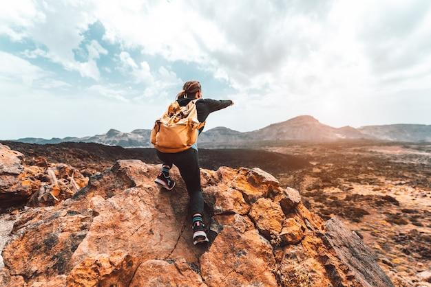 Mulher bonita alpinista no topo da montanha, apontando para o vale do sol. menina com mochila viajar sozinha na natureza.