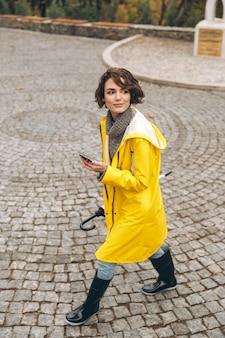 Mulher bonita andando no sett pelo parque da cidade com telefone celular e guarda-chuva nas mãos, aproveitando o dia de folga