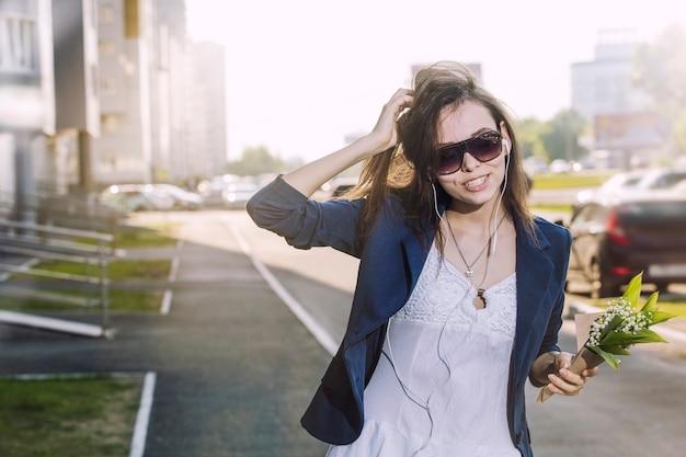 Mulher bonita andando pela cidade ouvindo música em fones de ouvido com um buquê de lírios nas mãos
