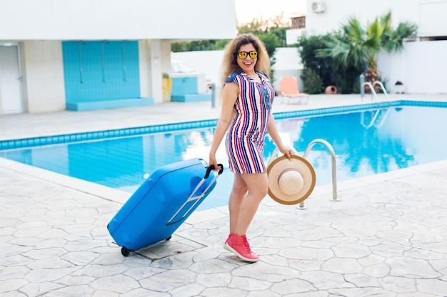 Mulher bonita andando perto da área da piscina com a bagagem.