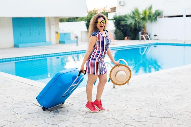 Mulher bonita andando perto da área da piscina com mala.