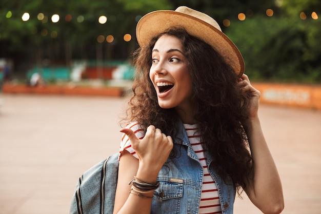 Mulher bonita animada com cabelo castanho encaracolado, rindo e apontando o dedo para o lado enquanto caminhava em um local moderno ou parque moderno com lâmpadas coloridas