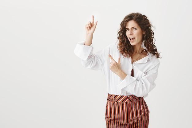 Mulher bonita animada dançando e apontando o dedo para cima