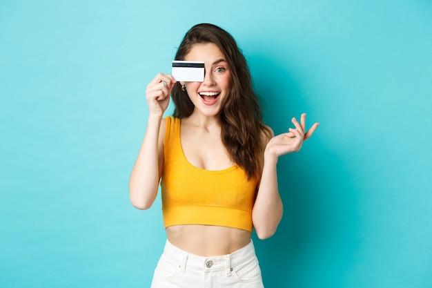 Mulher bonita animada em um top cortado de verão, olha maravilhada com a câmera, fazendo compras com cartão de crédito, em pé sobre um fundo azul