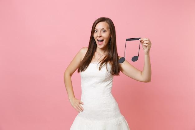 Mulher bonita animada em vestido branco segurando nota musical escolhendo staff, músicos ou dj