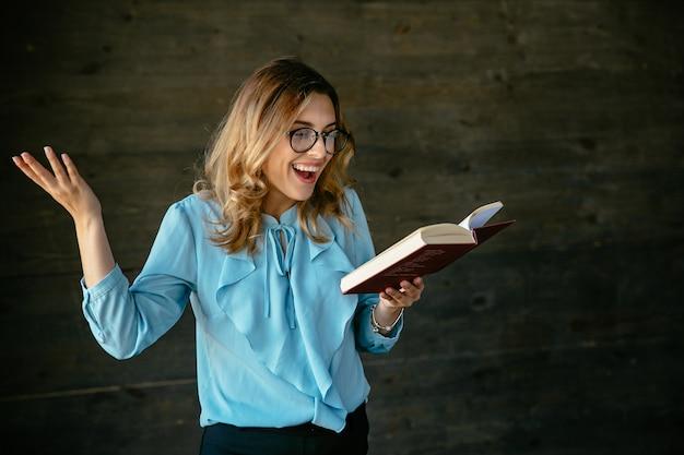 Mulher bonita animada rindo depois de ler algo novo e interessante no livro