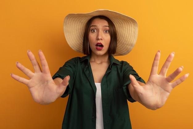 Mulher bonita ansiosa com chapéu de praia estendendo as mãos isoladas na parede laranja