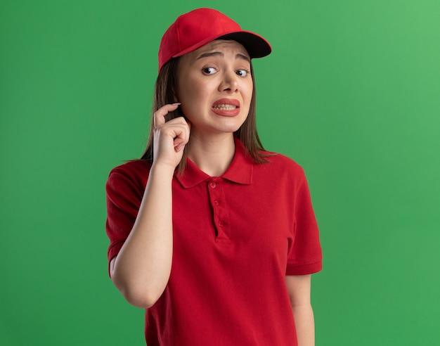 Mulher bonita ansiosa, entregadora de uniforme, de uniforme segura a mão perto do rosto e olha para o lado