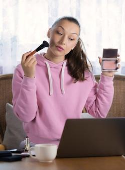 Mulher bonita anuncia novo blush rouge, faz publicidade em casa na frente do laptop