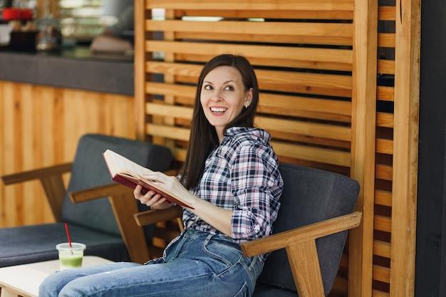 Mulher bonita ao ar livre rua verão café café de madeira sentado com roupas casuais, lendo livro com uma xícara de coquetel