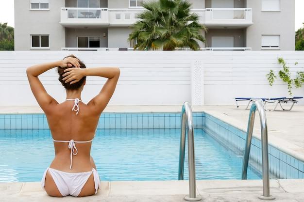Mulher bonita ao lado de uma piscina