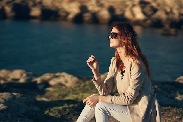 Mulher bonita ao pôr do sol no verão perto do mar nas montanhas vista recortada