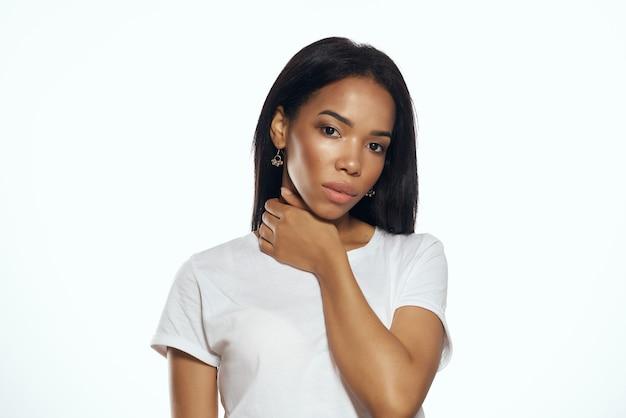 Mulher bonita aparência africana em cabelos longos de brincos de camiseta branca. foto de alta qualidade