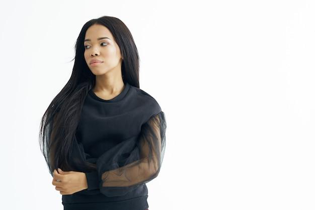 Mulher bonita aparência africana vestido preto cosméticos moda luz de fundo. foto de alta qualidade
