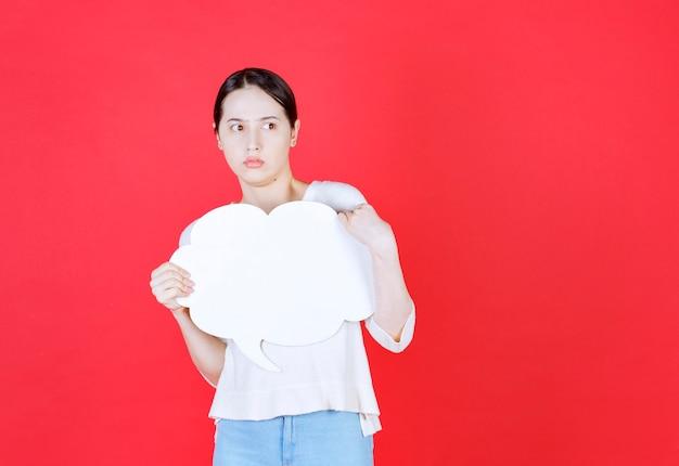 Mulher bonita apavorada segurando um balão de fala em forma de nuvem