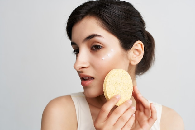 Mulher bonita aplicando creme com uma esponja no rosto, closeup