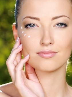 Mulher bonita aplicando creme cosmético na pele perto dos olhos