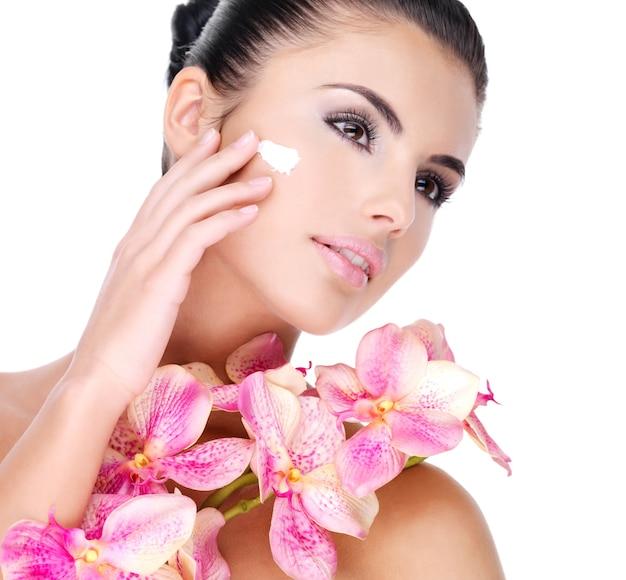 Mulher bonita aplicando creme cosmético no rosto com flores cor de rosa no corpo - isolado no branco