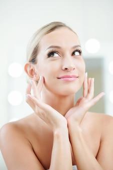 Mulher bonita aplicando creme facial