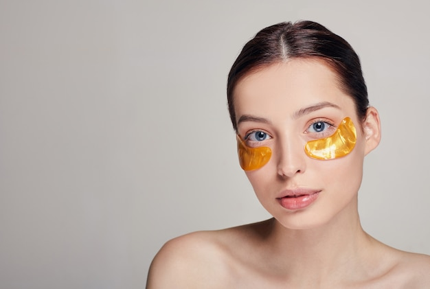 Mulher bonita aplicando manchas douradas de colágeno sob os olhos. remova rugas e olheiras. uma mulher cuida da pele ao redor dos olhos. procedimentos cosméticos.