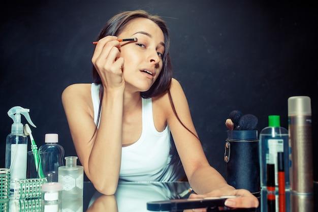 Mulher bonita aplicando maquiagem