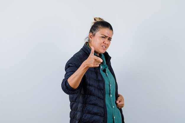 Mulher bonita apontando com o dedo indicador na camisa verde, jaqueta preta e parecendo com raiva. vista frontal.