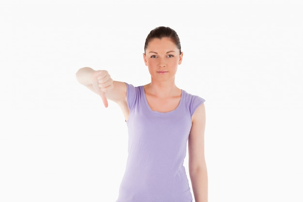 Mulher bonita apontando o polegar para baixo enquanto está de pé