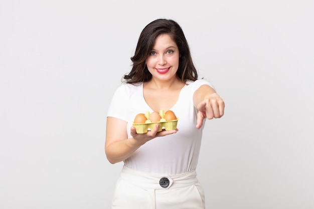 Mulher bonita apontando para a câmera, escolhendo você e segurando uma caixa de ovos