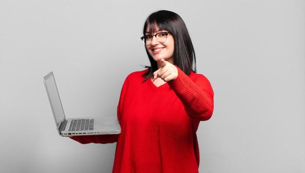 Mulher bonita apontando para a frente com um sorriso satisfeito, confiante e amigável, escolhendo você