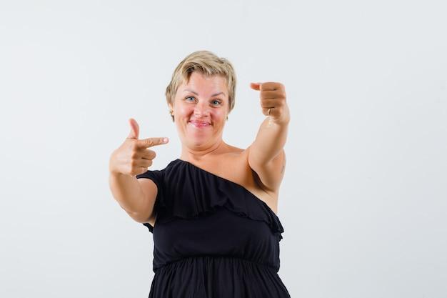 Mulher bonita apontando para a mão esquerda com uma blusa preta e parecendo satisfeita