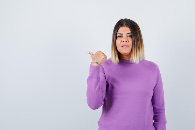 Mulher bonita, apontando para o lado com o polegar no suéter roxo e olhando confiante, vista frontal.